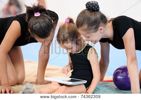 Three gymnast girls with tablet computer