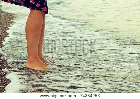 Beautiful Girl's Legs Walking On The Beach At The Sea