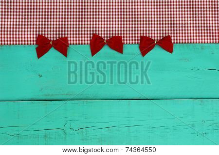 Blank antique green old wood sign with red checkered border and red velvet bows
