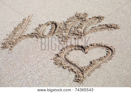 The word Love written on the sand with a hearth drawing