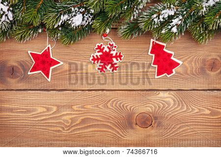 Christmas fir tree with snow and holiday decor on rustic wooden board with copy space