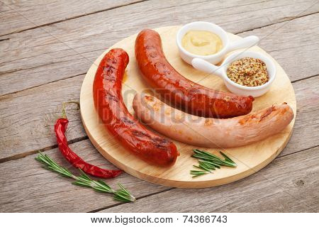 Various grilled sausages with condiments on cutting board