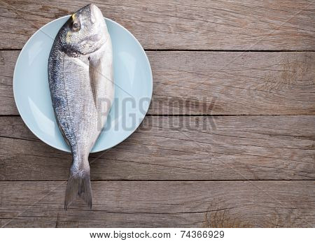Fresh dorado fish on wooden table with copy space