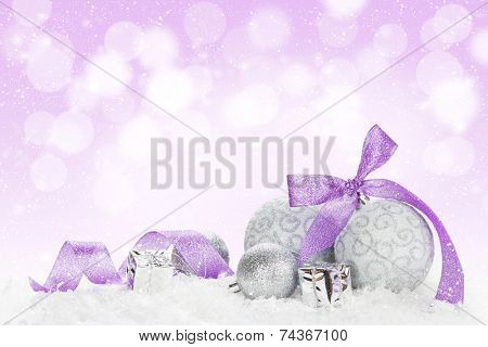 Christmas baubles and purple ribbon over snow bokeh background with copy space