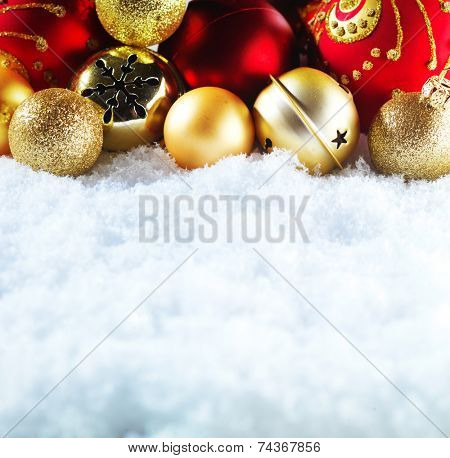 Winter and Christmas background. Beautiful sparkling golden and red Christmas decoration on a white snow background. Ornamental Christmas concept. Close up with copy space.