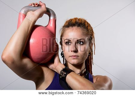 Portrait Close Up Of Young Attractive Female Doing Kettle Bell Exercise On Grey Background.