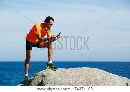 Young athlete in bright sportswear holding mobile smart phone