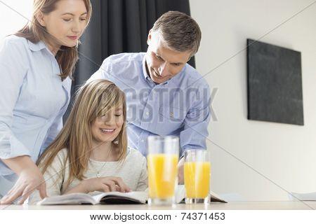 Happy parents assisting daughter in homework at home