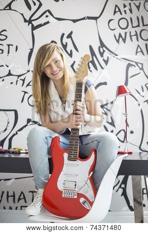 Full-length portrait of teenage girl with electric guitar sitting on study table at home