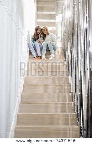 Full-length of sisters listening to music on stairway