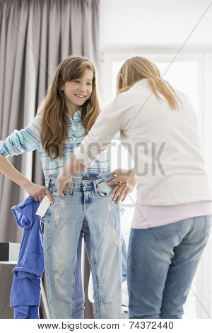 Sisters trying on clothes at home