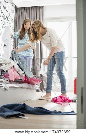 Sisters cleaning bedroom