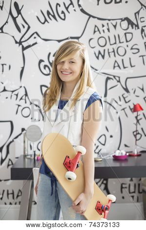 Portrait of happy teenage girl holding skateboard at home