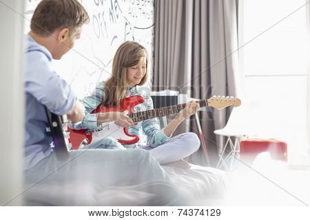 Father and daughter playing electric guitars at home