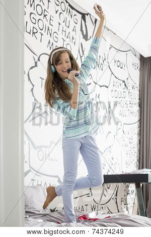 Full-length of girl listening music while singing into hairbrush on bed