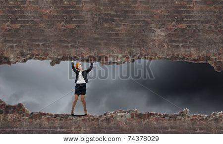 Young engineer woman lifting brick wall above head