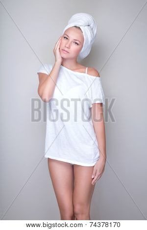 Beautiful woman with towel on head touching face isolated on gray background, natural facial cosmetics, health care and spa concept