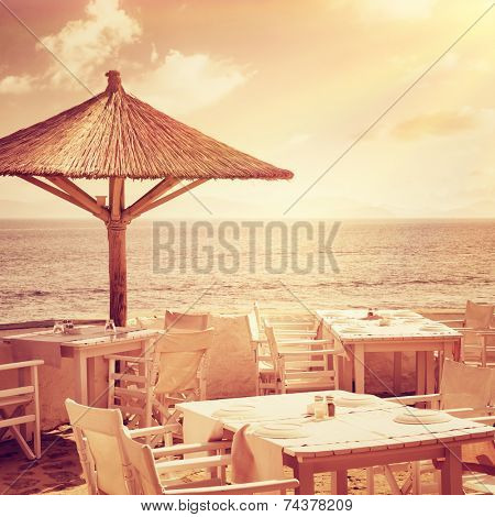 Cozy restaurant on the beach in mild sunset light, romantic dinner on tropical island, luxury beach resort, summer vacation concept