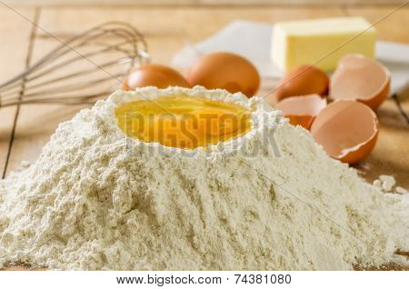 Flour, eggs, butter and a  whisk on a wooden background
