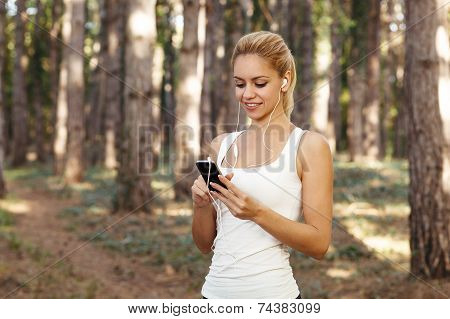 Young Woman Listening To Music Through Earbuds