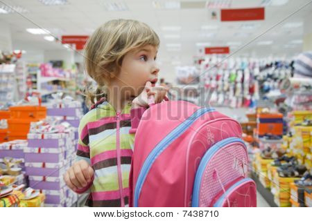little girl in supermarket choose footwear with school bag in hands