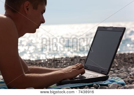 young man working on his notebook on beach.