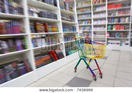 Bookshop interior. A in front of racks with books there is bright cart for purchases