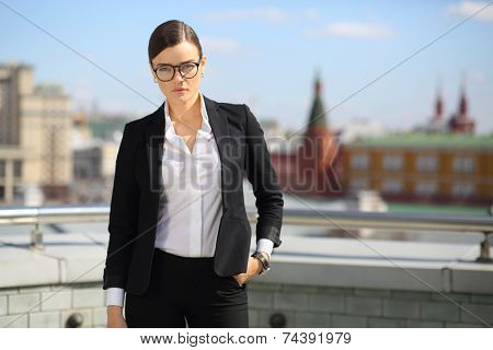 Portrait of beautiful businesswoman in glasses and black pantsuit on terrace overlooking Kremlin