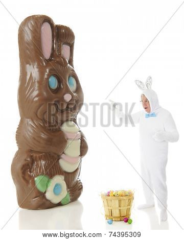 A senior man in a white rabbit outfit shocked while pointing to a giant chocolate bunny.  On a white background.