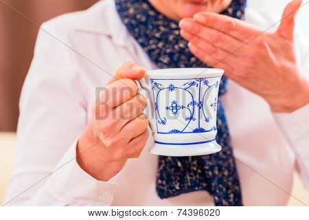 Old man drinking tea to cure bad cold or flu at home