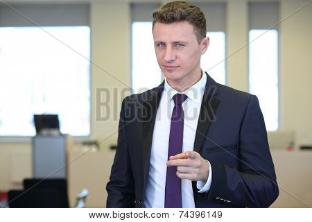 Businessman with distrustful look pointing at camera in the office