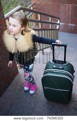 Pretty little girl standing with a large green suitcase on stairs