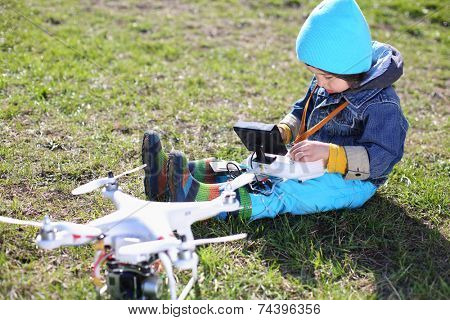 Little boy in blue hat sitting on grass with radio control in his hands and quadcopter