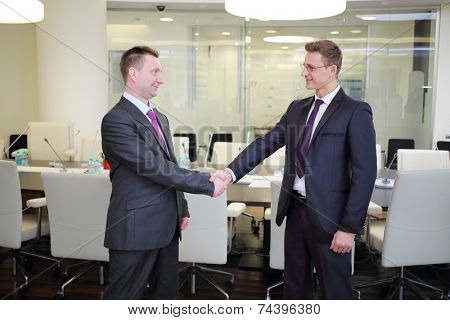 Two businessmen shaking hands in conference hall