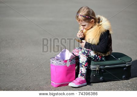 Little girl sitting on suitcase in middle of road and painting lips with lipstick