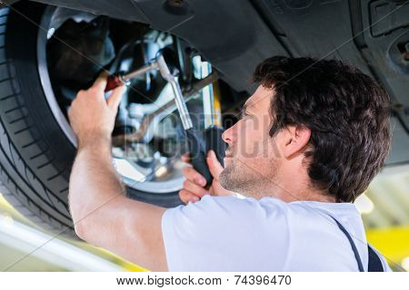 Mechanic working in car workshop on wheel