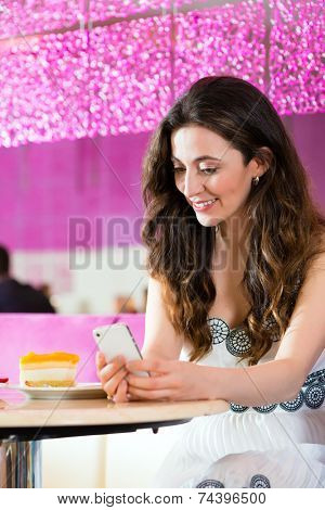 Young woman in a cafe or ice cream parlor using her phone, maybe she is single or waiting for someone