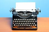 pic of typewriter  - Old typewriter on wood on a blue background - JPG