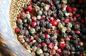 stock photo of peppercorns  - Red black green and white peppercorns mixed - JPG