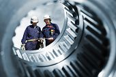 stock photo of mechanical engineer  - two engineers seen through a large cogwheels gear shaft - JPG