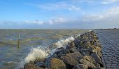 picture of dike  - Basalt stones along a dike in a stormy sea - JPG