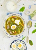 foto of sorrel  - Sorrel egg and sour cream soup in a plate on a table - JPG