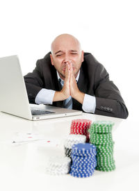 picture of spanish money  - desperate addict businessman on computer laptop loosing lots of money betting on internet poker with cards and chips on online gambling addiction isolated on white - JPG