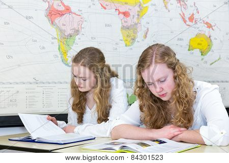 Two teenage girls studying in geography class