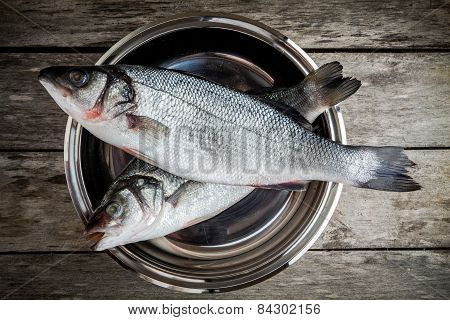 Two Raw Fresh Sea Bass In A Bowl On Wooden Table