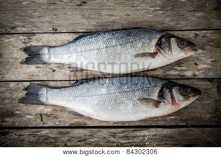 Two Raw Seabass On A Rustic Wooden Table