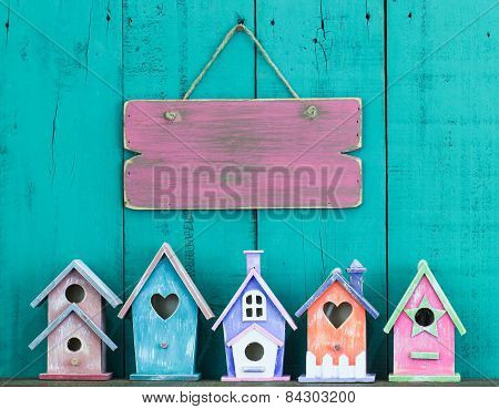 Blank sign hanging on fence by row of birdhouses