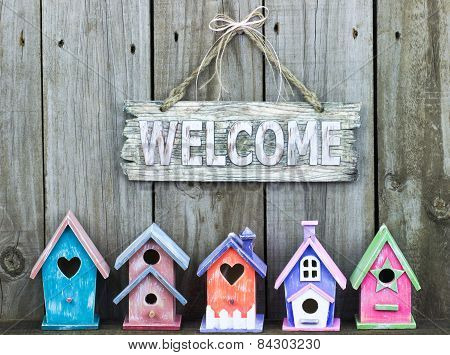 Welcome sign with bow by row of wooden birdhouses