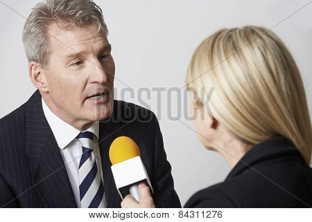 Businessman Being Interviewed By Female Journalist With Microphone
