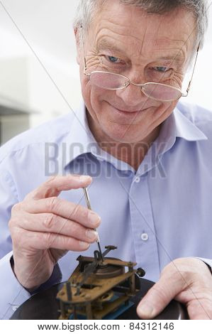 Senior Man Mending Clock Mechanism
